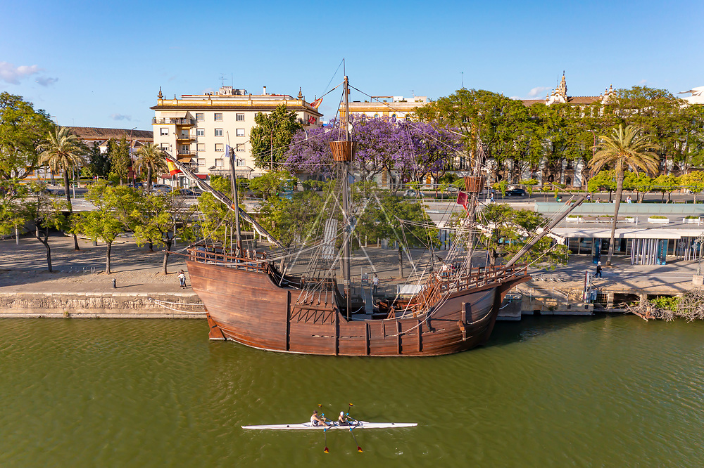 Seville, Spain - 12 May 2021: Aerial view of a docked sailboat and kayakers passing by on the Guadalquivir river in Seville, Andalusia, Spain.