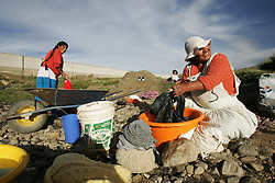 A woman washes clothes in Mariscal Sucre, a neighborhood in El Alto.   Many of the adobe homes in Mariscal Sucre have no running water and families are forced to collect rain water, use dirty wells or go to a nearby home with water.   The private water company, Aguas de Illimani, had their contract annulled by the Bolivian government after members of the politically powerful El Alto community took to the streets to protest poor service and high installation fees.