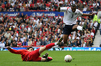 Photo: Paul Thomas.<br /> England v Macedonia. UEFA European Championships 2008 Qualifying. 07/10/2006.<br /> <br /> Ashley Cole (R) of England jumps to advoid the tackle of Goran Maznov.