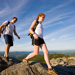 A young couple hiking on the summit of Mount Monadnock in New Hampshire's Monadnock State Park.