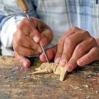 South America, Ecuador, San Antonio de Ibarra.  Woodcarver at work in his studio in San Antonio de Ibarra, in the Ecuadorian Andes.