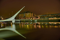 "Bridge ""La Mujer"" in Puerto Madero, Buenos Aires, with view of the docks and recycled buildings. The Bridge was designed by Santiago Calatrava and its a Landmark on this tourist destination in Buenos Aires."