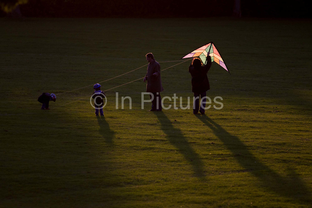 In late sunshine, a family of parents and two young children try to launch a stunt kite into the air in a south London park. The sun is low and catches the fabric of the kite's colours as mother holds its frame up in the air when the wind picks up. The park is a public space called Ruskin Park in London SE24, herne Hill, a local place for kids and parents in the inner-city borough of Lambeth.