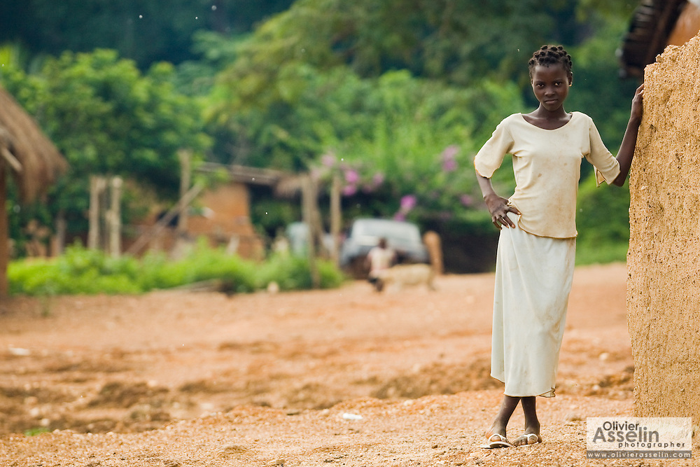 A teenage girl stands by a mud house in Tano Akakro, Cote d'Ivoire on Saturday June 20, 2009.