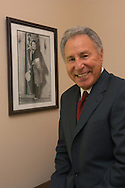 Television college football analyst Lee Corso stands next to a photo of his father at his home in Heathrow, Florida.