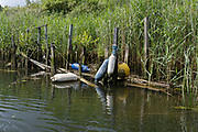 A riverside landscape of decaying wood, a private mooring structure in riverbank reeds on the river Yare, on 2nd July 2021, in Thorpe St Andrew, Norwich, England.