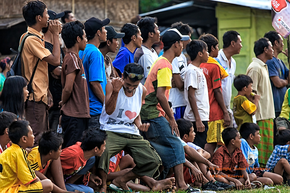 """Enthusiastic Contrarian: All eyes are to one side as fans intensely watch a football (soccer) game, save for one man, who wears an """"I love Bali"""" muscle shirt and enthusiastically pumps his arms in celebration, Bayan Lombok Indonesia."""