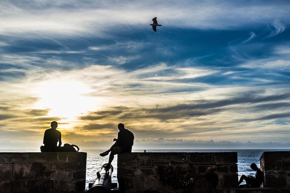 People enjoying sunset on rampart walls, Essaouira, Morocco.
