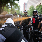 CHARLOTTE, NC - August 24: A Charlotte Mecklenburg police officer sprays an anti-racist protestor with pepper spray after trying to remove them from a road during a protest against the 2020 Republican National Convention in Charlotte, NC on August 24, 2020. Protests continued as the 1 day, in person convention began Monday afternoon and will end the same day after the party official re-nominates President Donald Trump and Vice President Mike Pence. The rest of the convention will go virtual. (Photo by Logan Cyrus for AFP)