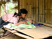 A young Hmong girl takes care of her sleeping baby sister, Ban Long Lan, Luang Prabang province, Lao PDR while her parents work processing bamboo shoots collect from the forest.