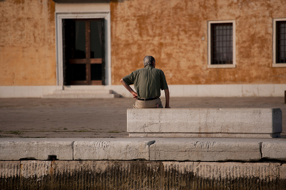 Rear view of a seated man relaxing by a Venice canal