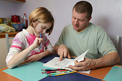Single parent helping young daughter with her homework in the kitchen,