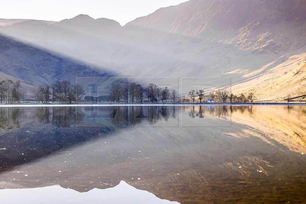 © Licensed to London News Pictures. 02/03/2021. Buttermere UK. The mountains that surround Buttermere lake in Cumbria reflect into the still water this morning as the sun send beams of light through the hills. Photo credit: Andrew McCaren/LNP