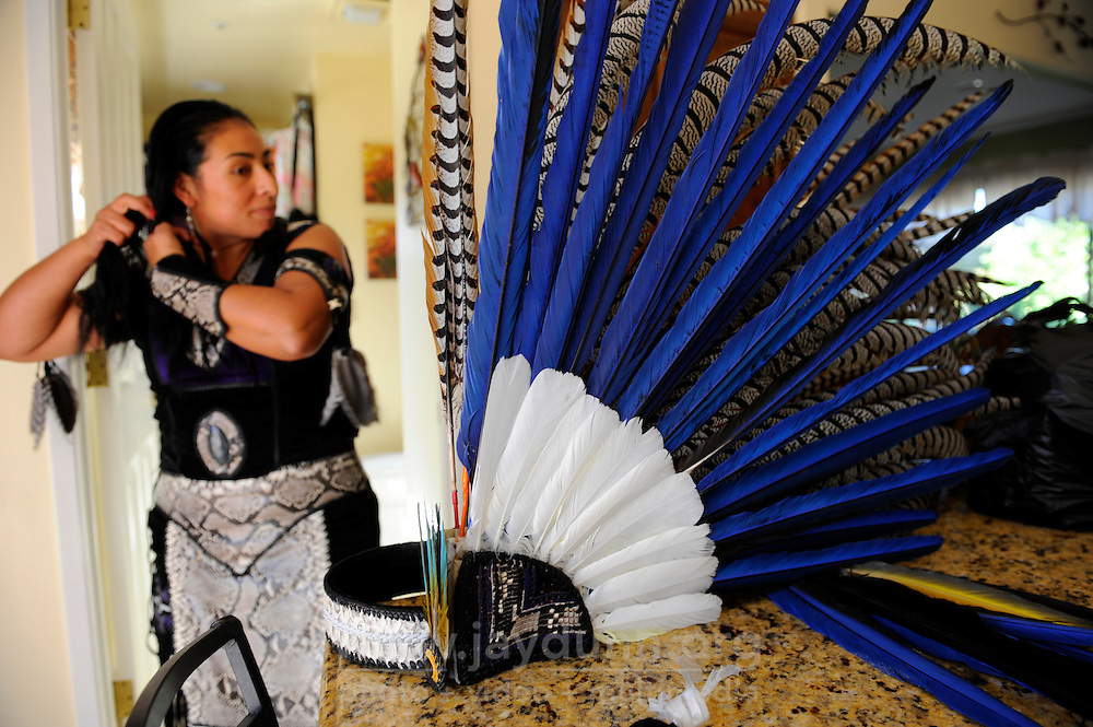 Yaocuauhtli member Ehecatl Chantico Moreno (Wind and Fire of the Home) shows the elements of her handmade outfit come together. The group's elaborate headdresses are assembled for each dance.
