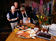 Chef Steve Lacroix serving seafood supper to Madeleine Kamman with Alan Kamma, Patty Park, Bob Griffin and Tom Dowd beyond, Winterlake Lodge seafood dinner, Alaska.