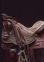 Embossed leather and suede saddle with bridle and stirrup tack hanging from the saddle horn.