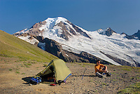 Hiker relaxing at an alpine camp on Chowder Ridge with Mount Baker (elevation 10,778feet (3,285m) in the distance. Mount Baker Wilderness Washington USA