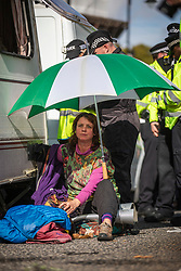 © Licensed to London News Pictures. 15/10/2019. London, UK. An Extinction Rebellion protester locked on to a caravan shelters beneath an umbrella, as demonstrators block Millbank. Police have said that any Extinction Rebellion protesters who continue will be liable for arrest. Photo credit: Rob Pinney/LNP