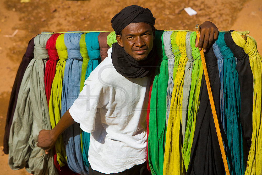 Street vendor selling colored fabrics. At the confluence of the Niger and the Bani rivers, between Timbuktu and Ségou, Mopti is the second largest city in Mali, and the hub for commerce and tourism in this west-african landlocked country.
