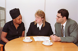 Multiracial group of office workers sitting around table having business meeting,