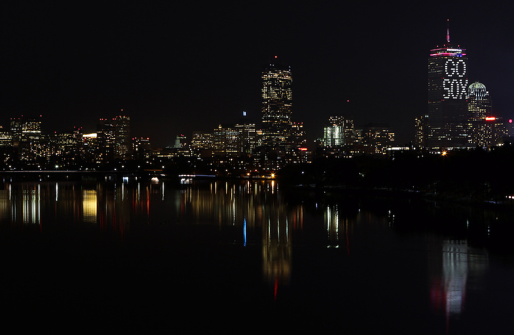 Boston skyline photography showing the Prudential Center with a Go Sox message, 111 Huntington Avenue office building, John Hancock Tower and Beacon Hill dark night reflection in the Charles River of the Boston Red Sox versus ST. Louis Cardinals World Series playoff game 6 on 30 October 2013 in Boston. <br /> <br /> Prudential Center lights are lit up with the message Go Sox towering over the great city of Boston.<br /> <br /> This Boston night photography image of the  Prudential Center with a Go Sox message is available as museum quality photography prints, canvas prints, acrylic prints or metal prints. Prints may be framed and matted to the individual liking and wall decoration needs: <br /> <br /> http://juergen-roth.artistwebsites.com/featured/go-sox-juergen-roth.html<br /> <br /> Good light and happy photo making!<br /> <br /> My best,<br /> <br /> Juergen<br /> http://www.exploringthelight.com<br /> http://www.rothgalleries.com<br /> @NatureFineArt<br /> http://whereintheworldisjuergen.blogspot.com/<br /> https://www.facebook.com/naturefineart