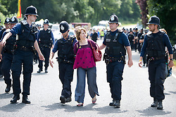© London News Pictures. 27/07/2013. Balcombe, UK.  A woman being arrested in handcuffs during an Anti Fracking demonstration by activists and local villagers attempting to blockade a drilling site in Balcombe, West Sussex which has been earmarked for fracking. A number of demonstrators at the site have been arrested. Photo credit: Ben Cawthra/LNP
