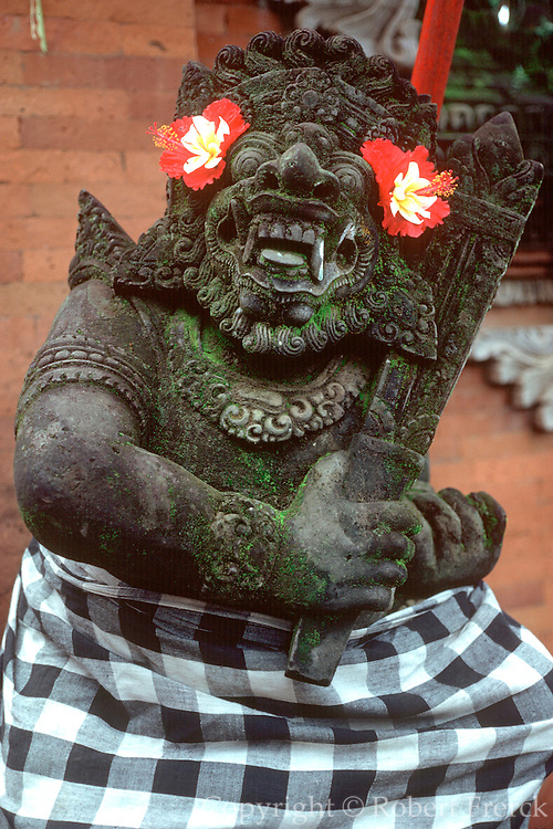 INDONESIA, BALI a statue of a guardian figure clothed in traditional checked cloth and fresh flowers guards the doorway of the villae temple