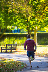 A runner does laps around Queens Park, North West London, as the early morning sunshine illuminates the leaves of trees as autumn colours begin to set in. London, October 01 2018.