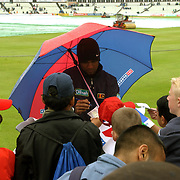 Sri Lanka's Nuwan Zoysa signs npower hit cards under his umbrella as play is delayed at Edgbaston due to the wet weather.