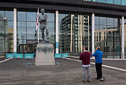 Two football fans pay their respects to the statue of English football's most loved player, Bobby Moore, on 6th November 2019, in Wembley, London, England. Sir Bobby Moore captained England to its World Cup victory against Germany at the old Wembley stadium in 1966.
