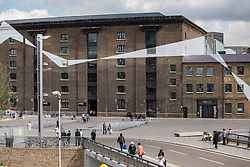© licensed to London News Pictures. London, UK 16/05/2013. Swiss artist Felice Varini's 'Across the Buildings' artwork installation consists of a series of monumental metallic geometric shapes which runs 542 metres on heritage buildings of Granary Square in King's Cross, London. From street level the shapes appear arbitrary, however from a single viewpoint they will unify into one contiguous pattern. Photo credit: Tolga Akmen/LNP