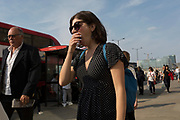 A lady yawns while commuters walk southwards over London Bridge, from the City of London - the capital's financial district founded by the Romans in the 1st century - to Southwark on the south bank, on 3rd September 2018, in London, England.