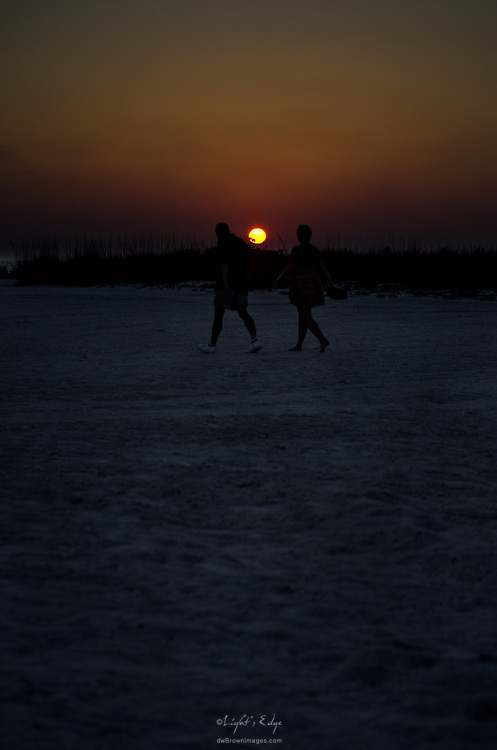 A couple walk the beach in St. Pete Beach as the sunsets over the Gulf of Mexico.