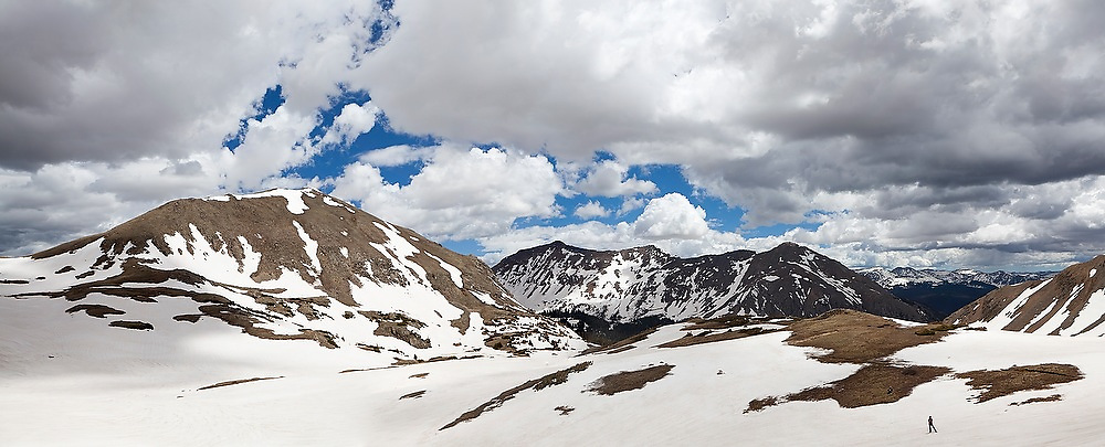 A hiker stands in the alpine basin at Parika Lake, Never Summer Wilderness, Colorado. Paprika Peak, Mount Nimbus, Mount Stratus and Baker Mountain rise prominently in the background.