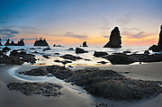 Point of Arches, Shi Shi Beach, Washington.   This is one of the most remote beaches in the country.  I came here twice, and knew I had to spend the night the next time, to capture it the way I wanted.  It is two miles with a backpack from the trailhead, the last of it down a not-quite cliff, with heavy rope to get you through the worst of it.  Out of the woods and then over, and through, massive piles of huge, bleached logs, several feet thick, piled 10 to 15 feet high like pick-up stix, trees that washed into the ocean to be stripped bare and tossed back up to the tree line by massive Pacific storms.  And  now you are on Shi Shi Beach, impossibly long and wild.  You walk a mile and a half to get closer to the end of it, and set up camp high above the tide line and marvel at just how far out there you really are, with no one else in sight.  And then march another mile down the sand to Point of Arches. They say that millions of years ago, the forested headland, just a bit behind me, stretched out to that far, far stack on the horizon.  Wind and water, night and day,  worked at it for millenia, until it broke and broke, again and again, and left these skeletal remains.  Sea stacks, some with forest still attached. How long did this great mass stand before crumbling to these remnants?  I still stand...unbroken, but not untouched. I can hear the incessant break of water, feel the wind.  In my world, it is love, loss, passion and pain that are inescapable, breaking us down.  I am only in this one overnight.