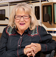 Editorial portrait of a wonderfully happy older woman with blond hair and glasses seated with hands clasped wearing a blue jean dress. Oh, and there is an RV in the background.