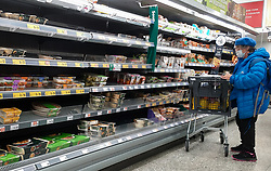 © Licensed to London News Pictures. 09/10/2021. London, UK. A shopper looks at nearly empty shelves of pre-cooked meat products in Morrisons, north London amid fears of food shortages leading up to Christmas due to labour shortages following Brexit. According to figures from the Office of National Statistics, one in six people in the UK have been unable to buy essential foods in the past two weeks and the Army could be drafted in to drive HGVs over Christmas as the supply chain crisis continues. Photo credit: Dinendra Haria/LNP