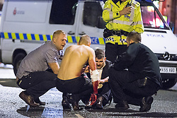 © Licensed to London News Pictures . 21/12/2013 . Manchester , UK . A man sits in the road and another with a bleeding arm following a fight on the city's Charlotte Street . Christmas revellers out in the rain in Manchester on Mad Friday , the last Friday night before Christmas which is typically one of the busiest nights of the year for police and ambulance crews . Photo credit : Joel Goodman/LNP
