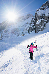 Woman carrying her ski and walking in snow, Bavaria, Germany, Europe