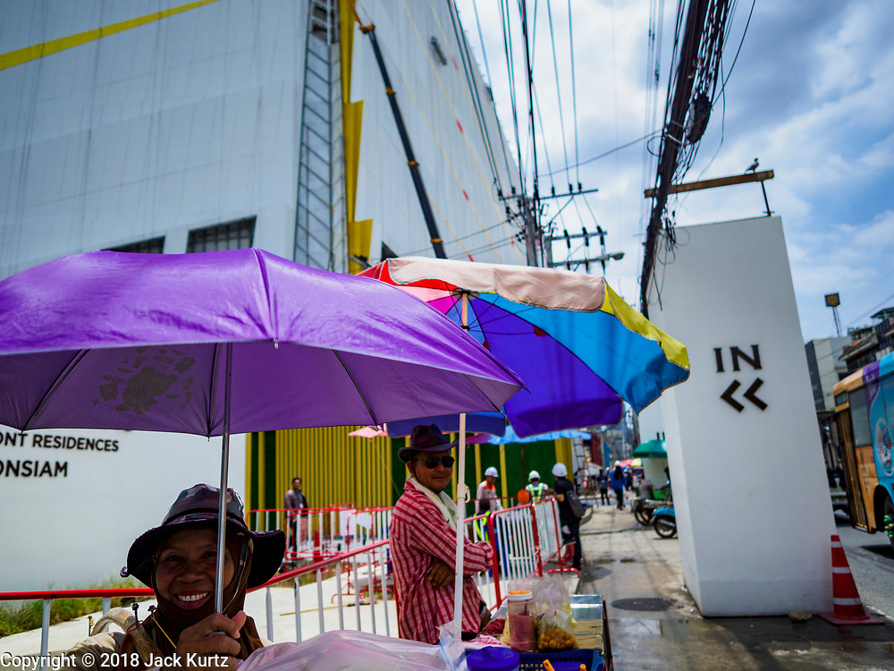 17 SEPTEMBER 2018 - BANGKOK, THAILAND: Food venders whose customers are construction workers from the ICONSIAM construction site in front of the site on Chareon Nakhon Road in Thonburi. ICONSIAM is a mixed-use development on the Thonburi side of the Chao Phraya River. It is expected to open in 2018 and will include two large malls, with more than 520,000 square meters of retail space, an amusement park, two residential towers and a riverside park. It is the first large scale high end development on the Thonburi side of the river and will feature the first Apple Store in Thailand and the first Takashimaya department store in Thailand.   PHOTO BY JACK KURTZ
