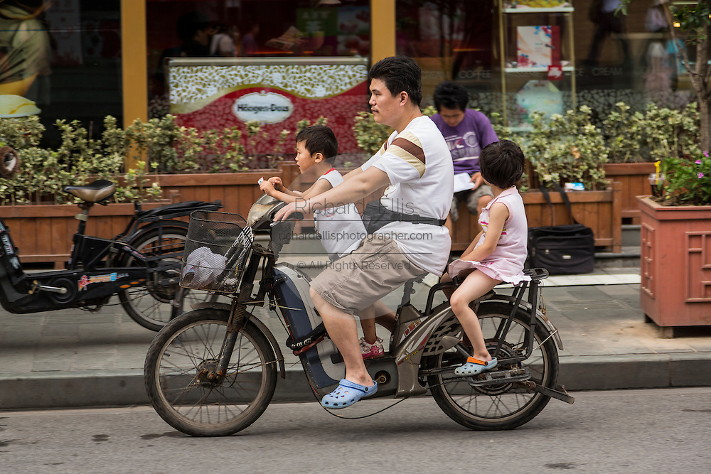 A family rides an electric scooter Shanghai, China