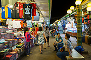Shoppers look around and market sellers sit on benches inside the Siem Reap Art Centre Night Market in Siem Reap, Cambodia, Asia. This market was opened in 2012.