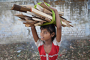 Poonam, 10, carrying firewood collected from a local vendor, is walking back to her newly built home in Oriya Basti, one of the water-contaminated colonies in Bhopal, central India, near the abandoned Union Carbide (now DOW Chemical) industrial complex, site of the infamous '1984 Gas Disaster'.