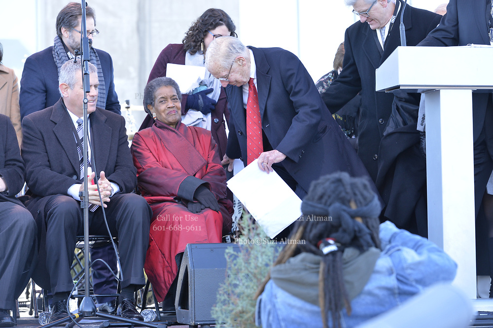 """Photo ©Suzi Altman 12/9/17 Jackson,MS       Myrlie Evers- Williams widow of slain civil rights icon Medgar Evers, left is joined on the podium by Governor William Winters, right, at the opening of the Mississippi Civil Rights Museum. Myrlie Evers dedicated her late husband Medgar Evers archival papers to the MS Department of Archives and History, which helped established the museum.  Evers spoke to the crowd outside after President Trump made private remarks inside to a closed audience of invited guests and press only. <br />  Right before the ribbon cutting ceremony outside on the podium Mrs Evers said """" These museums are priceless, going through the museum of my history I felt the bullets and the fears, but I also felt the hope."""" President Trump had a very short private tour of the Civil Rights Museum and did not mingle outside or stop to talk with any visitors to the new Civil Rights  museum. Photo©SuziAltman"""