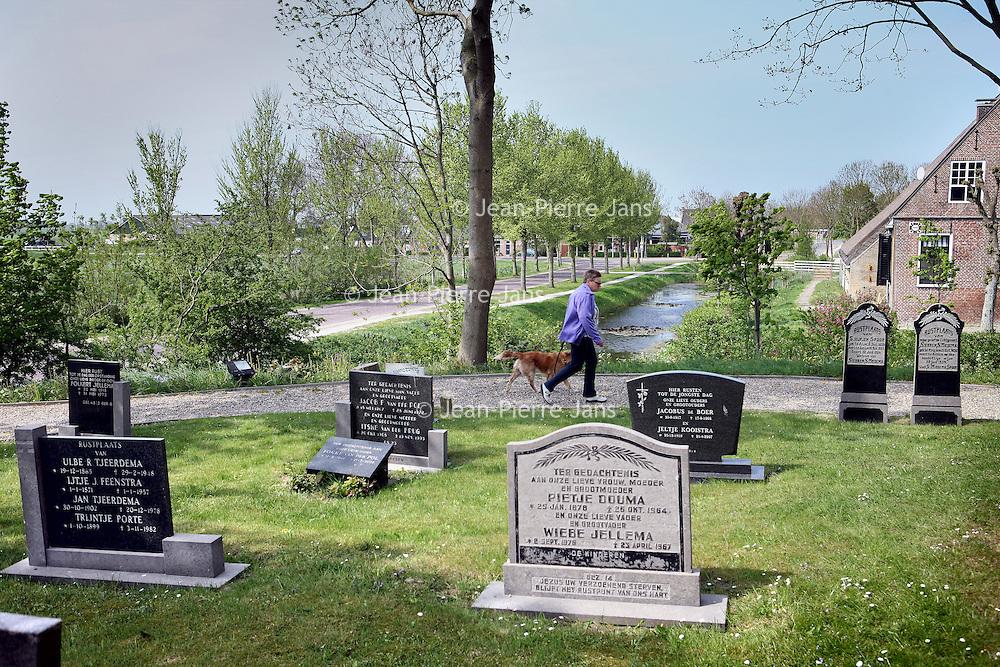 Nederland, Achlum , 27 april 2011..De begraafplaats bij de kerk van Achlum..Achlum is een dorp, dat vanaf 1 januari 1984 bij de gemeente Franekeradeel behoort, in de provincie Friesland (Nederland). Het is een terpdorp aan de Slachtedyk met ongeveer 635 inwoners (2009)..Achlum ligt ten zuidoosten van Harlingen en ten zuidwesten van Franeker..Om te vieren dat Achmea tweehonderd jaar geleden door Ulbe Piers Draisma in Achlum werd opgericht, organiseert de verzekeraar op 28 mei 2011 de Conventie van Achlum. Allerlei sprekers hebben toegezegd naar Achlum te komen, waaronder Bill Clinton, oud-president van de Verenigde Staten. Alle bewoners van het dorp worden bij de festiviteiten betrokken..Foto:Jean-Pierre Jans