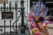 Dancers relax on a doorstep as they prepare for the parade - The Monday of the Notting Hill Carnival. The annual event on the streets of the Royal Borough of Kensington and Chelsea, over the August bank holiday weekend. It is led by members of the British West Indian community, and attracts around one million people annually, making it one of the world's largest street festivals.