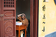 Buddhist monk studying at Longhua Temple in the south of Shanghai, China. This is a working temple where public come to burn incense, offer gifts and to eat. Located on Longhua Road, the temple was first built in 242 AD, during the period of the Three Kingdoms. Longhua Temple is the oldest temple in Shanghai and also the largest at 20,000 square metres including it's grounds. Because of several destructions by the wars, most of the buildings in Longhua Temple were reconstructed during the reign of the Emperor Tongzhi and Guangxu during the Qing Dynasty.