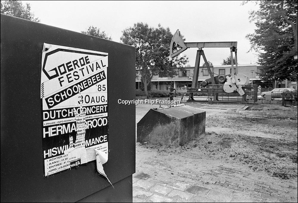 Nederland, Schoonebeek, 15-10-1985<br /> Jaknikker in Schoonebeek. Door de NAM gebruikt om olie op te pompen uit de grond. Onder Schoonebeek en omgeving zit het grootste olieveld van het vaste land van Europa . Tot 1996 werd hier met deze techniek olie gewonnen,  maar de winning was met de jaknikkertechniek niet meer rendabel. Een affiche van het Goeroe festival waar Herman Brood and his wild romance eerder dat jaar speelden .<br /> the Netherlands, <br /> Pump jacks known as nodding donkeys in the oil field by Schoonebeek. All pumpjacks disappeared from the landscape .