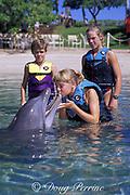 children greet a captive bottlenose dolphin, Tursiops truncatus, at Dolphin Quest at the Hilton Waikoloa Village, South Kohala, Kona Coast, Hawaii Island, USA