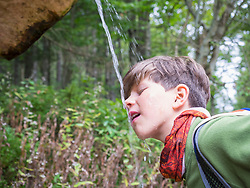 Girl drinking water from source in black forest, Feldberg, Baden-Württemberg, Germany